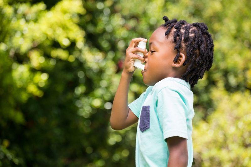 little boy uses inhaler outside