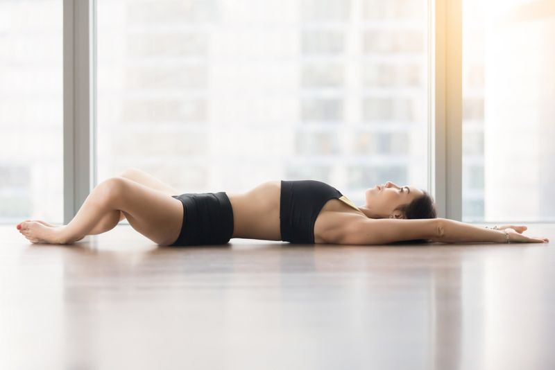 woman in reclined butterfly or bound angle stretch