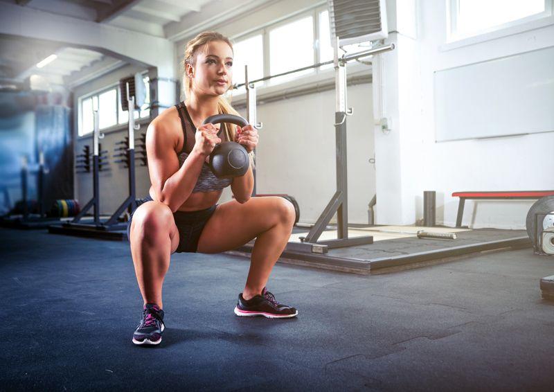 woman in gym doing kettlebell goblet squat exercise