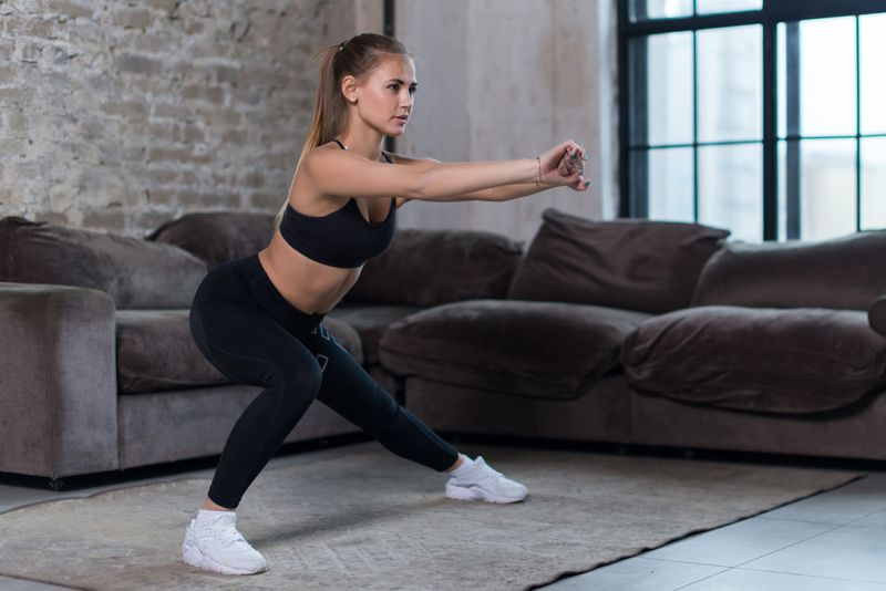 young woman doing adductor or inner thigh stretch at home