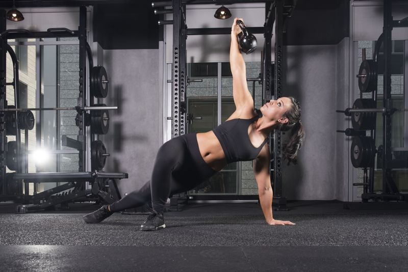 woman performing turkish getup in weight room with kettlebell
