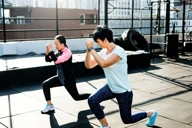 two women doing lunges in outdoor gym