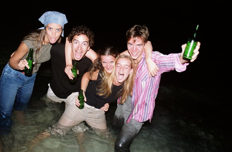 Group of young people in sea holding bottles of beer, portrait
