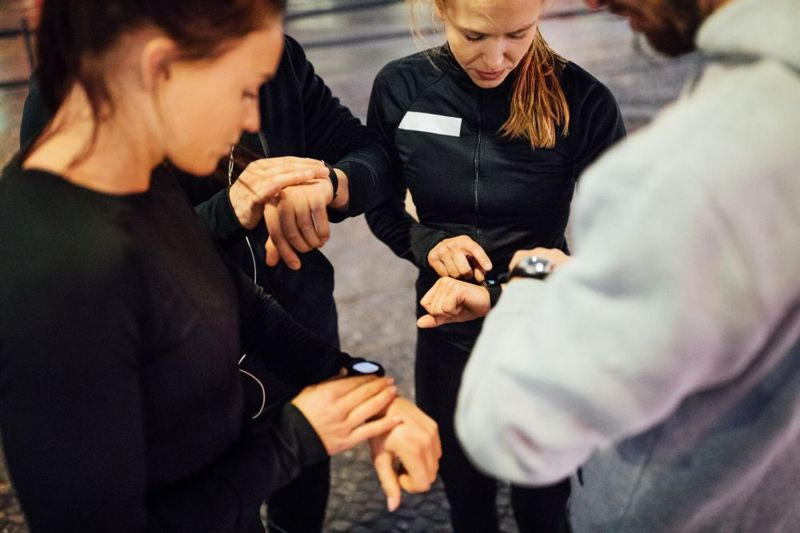 group of people checking fitness trackers together