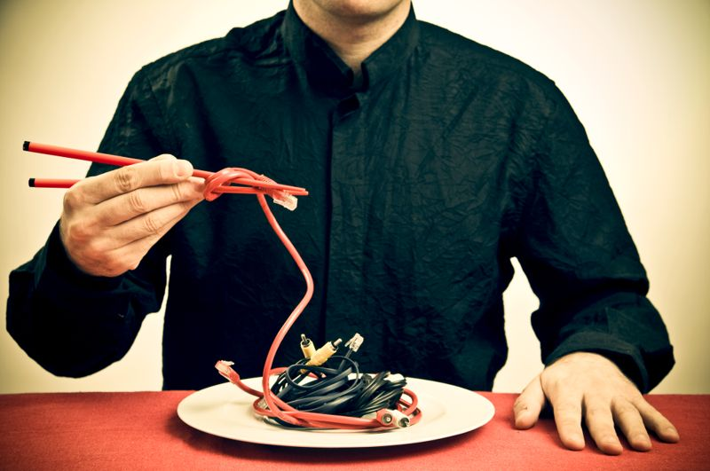 Man eating cables with chop sticks.