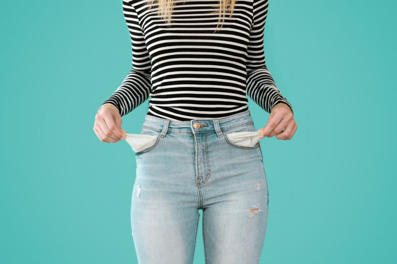 Close-up of young woman showing doesn't has nothing in her jeans pockets on blue background.