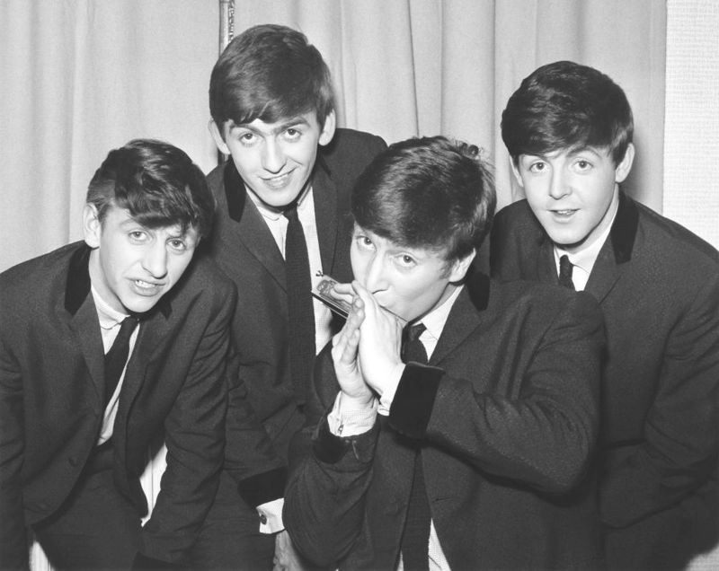 The Beatles pose for an eraly group portrait, backstage, (L-R) Ringo Starr, George Harrison, John Lennon (palying harmonica), Paul McCartney, 1962.