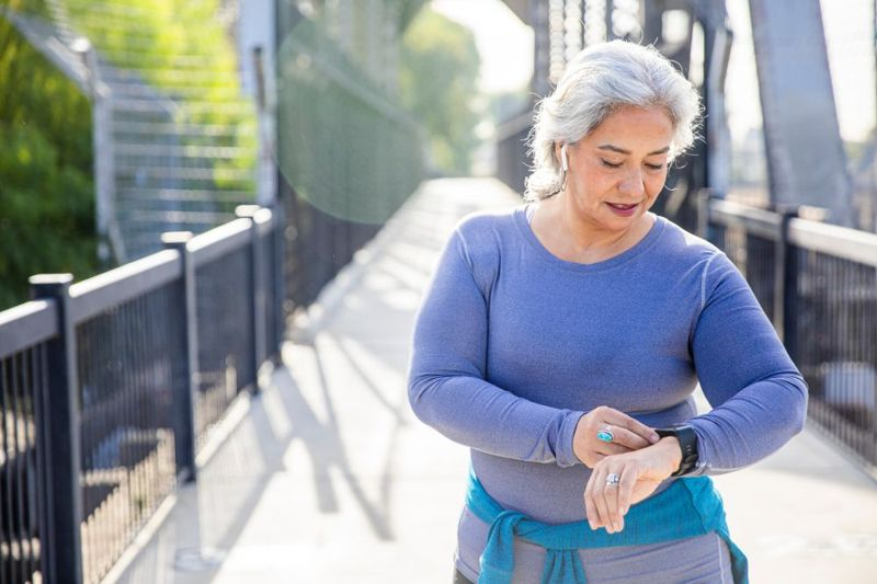 woman exercising outside checking fitness tracker