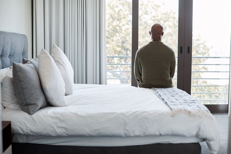 man looking out window sitting at foot of bed; depression concept