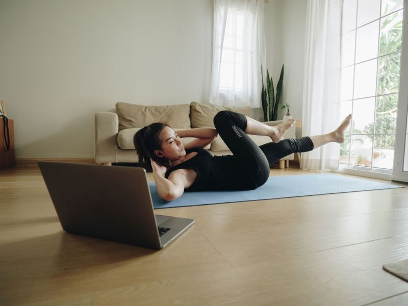 woman doing pilates at home watching video