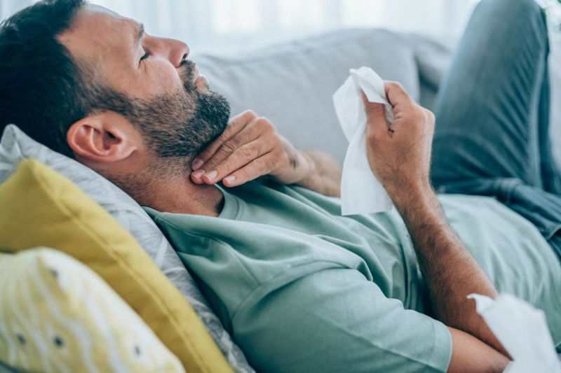 middle aged man with sore throat lying on couch