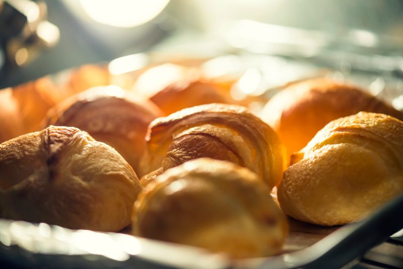 Croissants baking in the oven. Light source if the light bulb in the oven.Shallow depth of field.