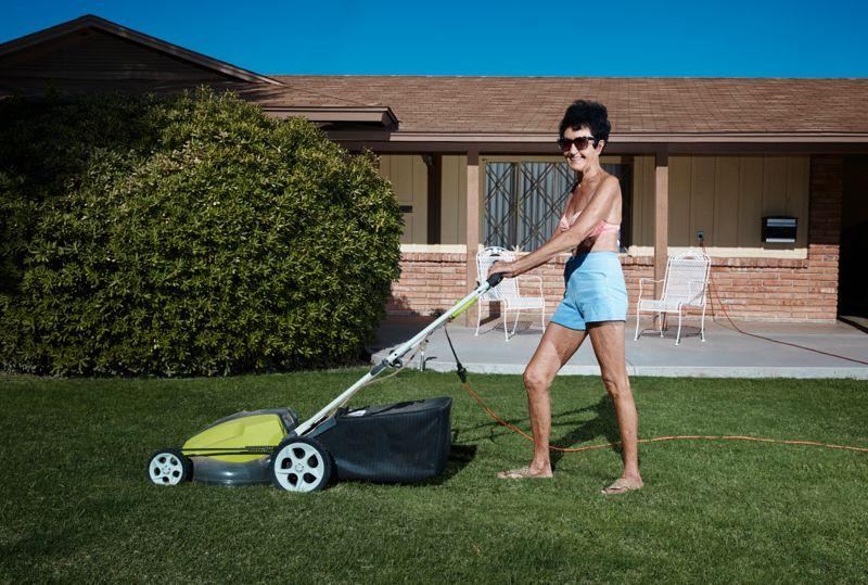 Attractive senior woman mowing lawn in bikini top.