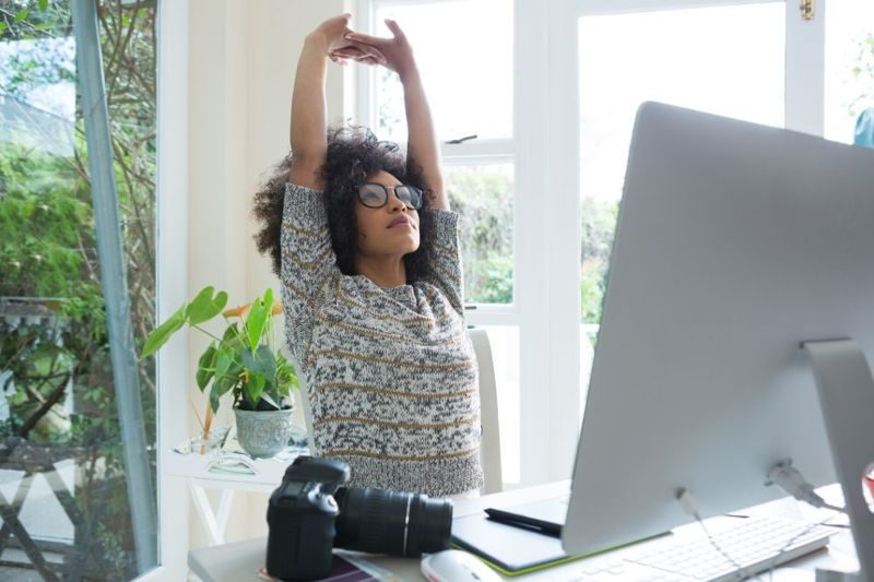 woman stretching while sitting at home office