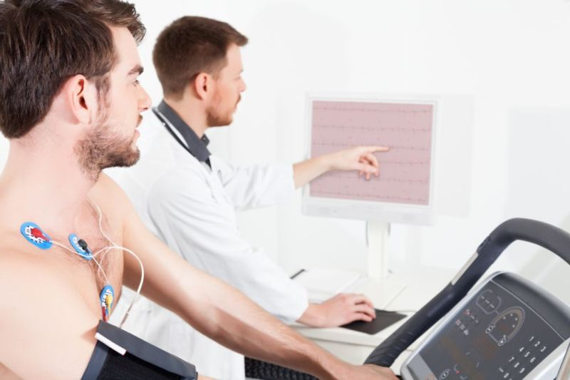young man on treadmill, doctor looking at heart rate