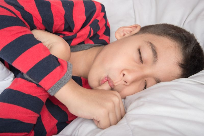 young boy sleeping and sucking his thumb