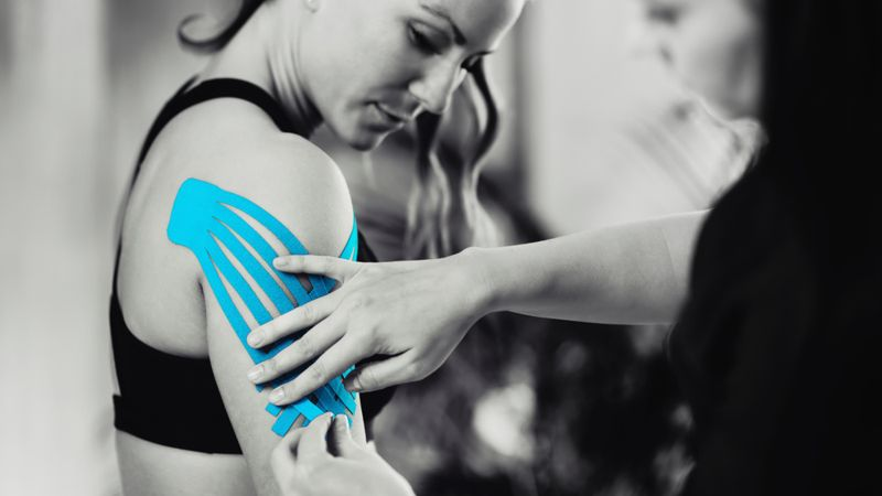 therapist placing fan kinesio tape on woman's outer arm