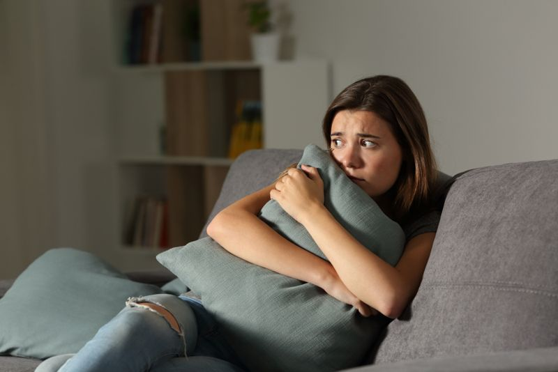 frightened young woman on couch hugging a pillow