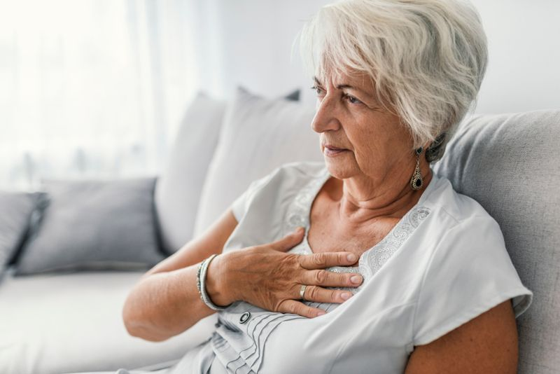 older woman on couch with her hand on her chest