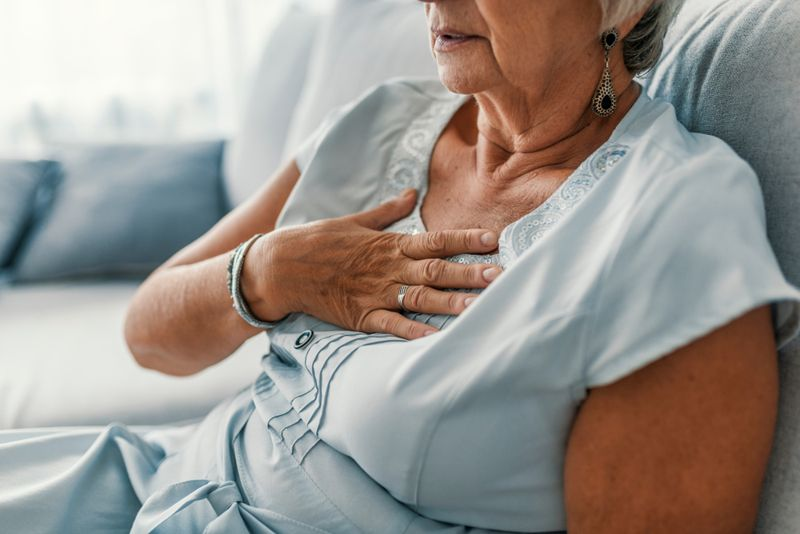 older woman on couch with hand on her chest, chest pain