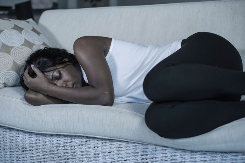 young, sad woman curled up on couch