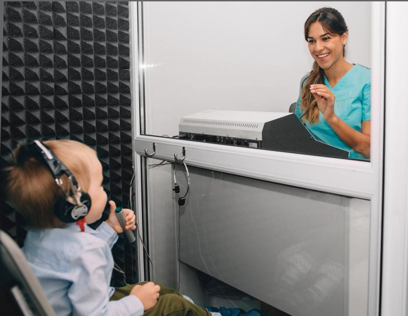 toddler getting a hearing test by an audiologist