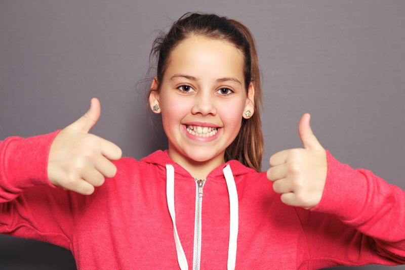 young girl giving thumbs up