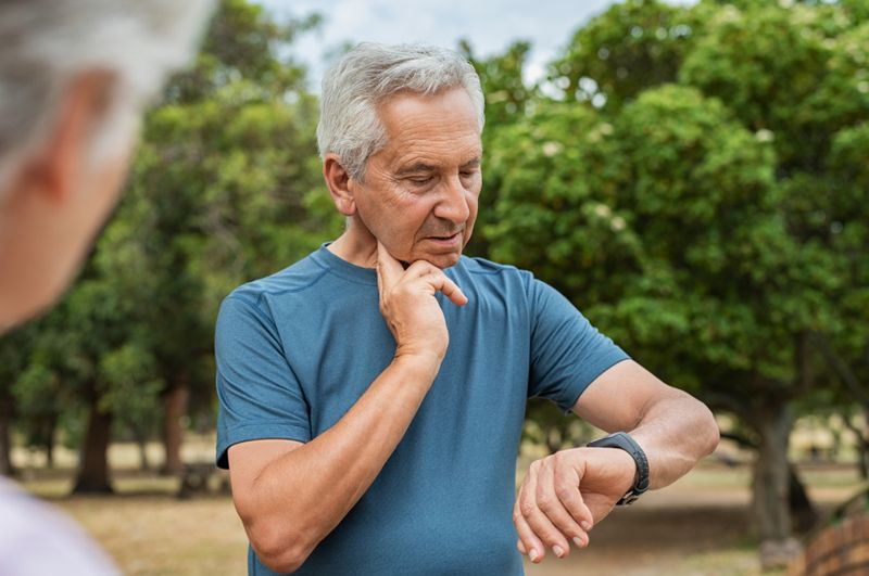 older man taking pulse at neck and looking at watch