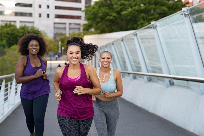 three women jogging on the sidewalk