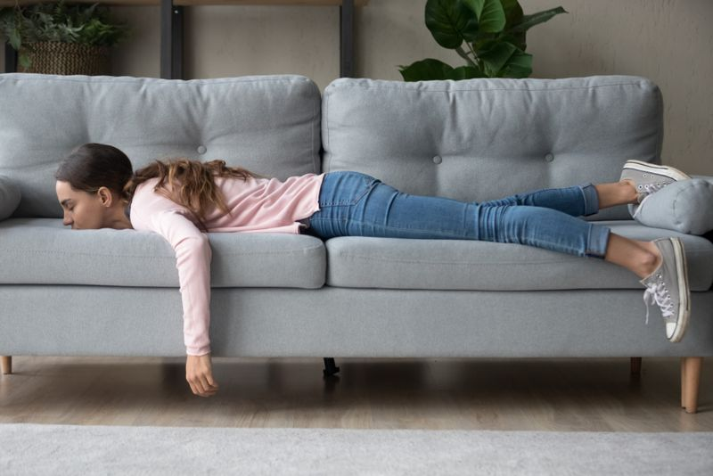exhausted and weak woman lying on couch