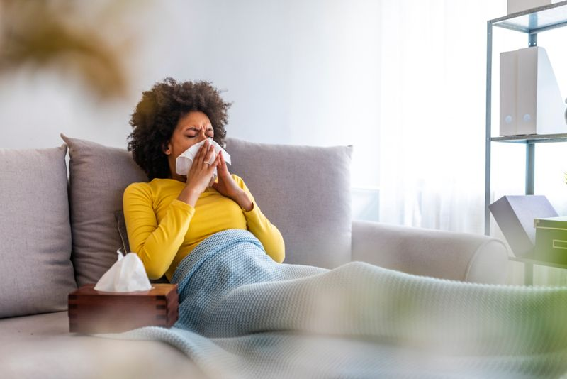sick woman on couch blowing nose