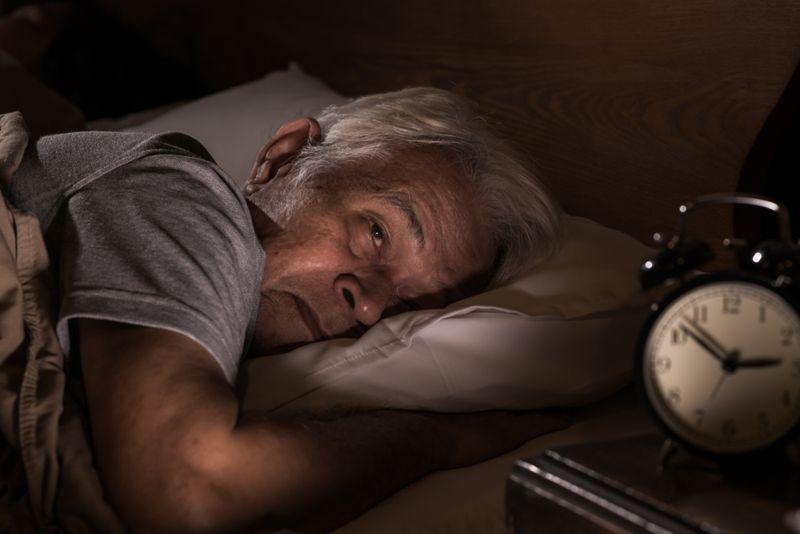 man lying awake in bed at 3 am