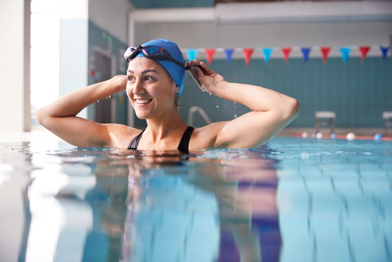 woman with swim cap and goggles in indoor pool
