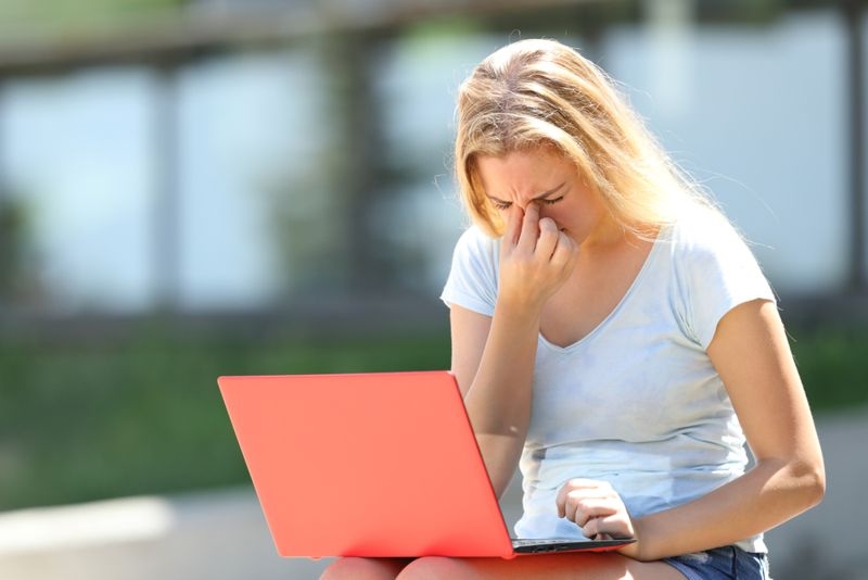 teenage girl with laptop rubbing her sore eyes
