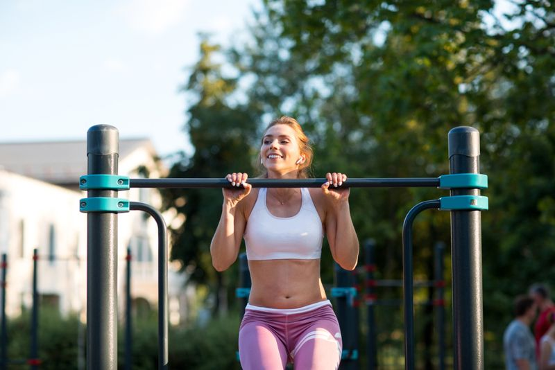young woman doing pullups at an outdoor jungle gym