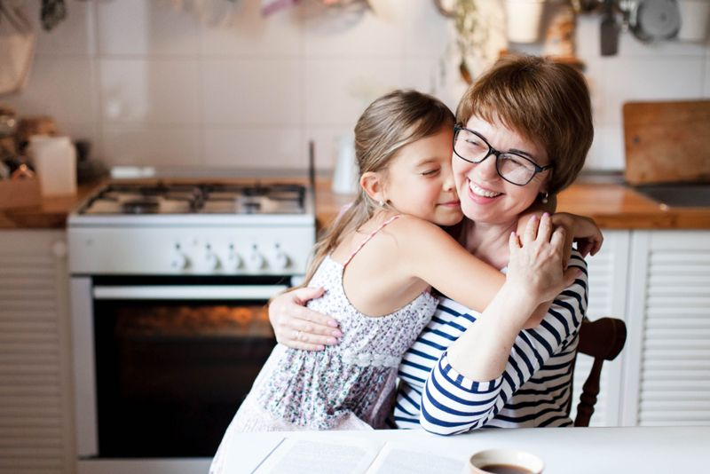 smiling woman and little girl in kitchen, hugging