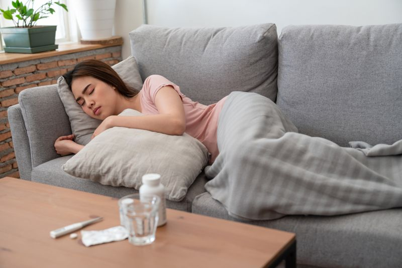 sick woman sleeping on couch