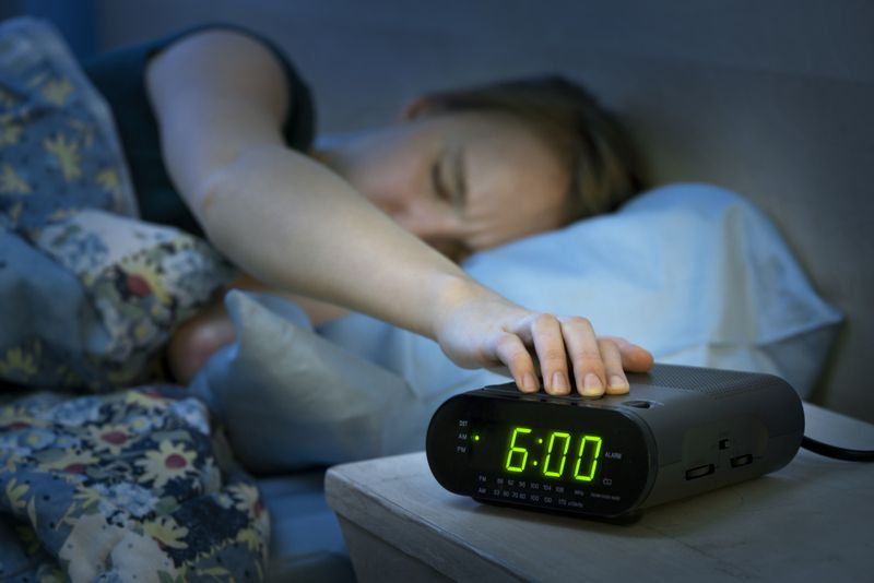 person in bed pressing snooze on alarm clock