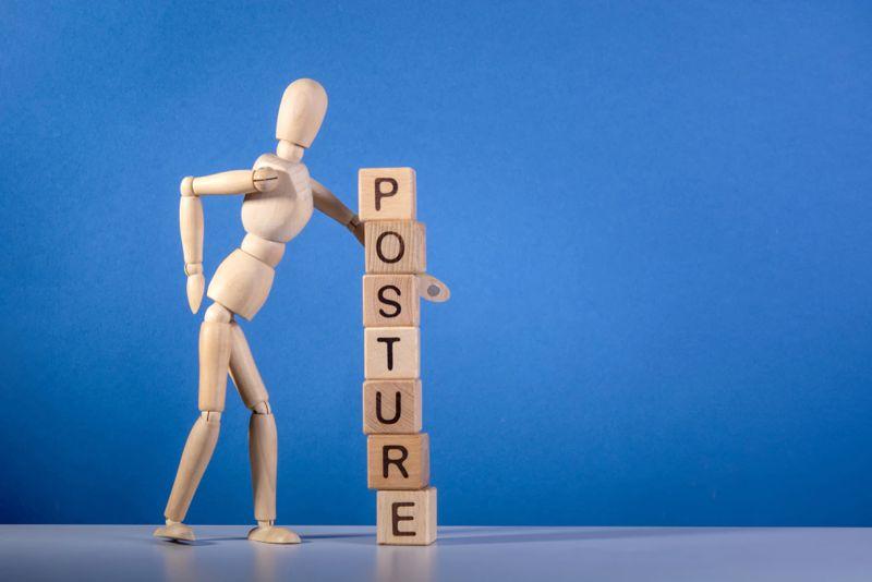 wooden mannequin beside wood blocks reading posture