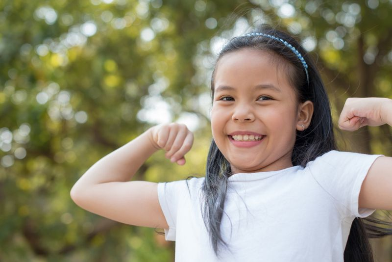 """young girl grinning and making """"strong"""" gesture"""