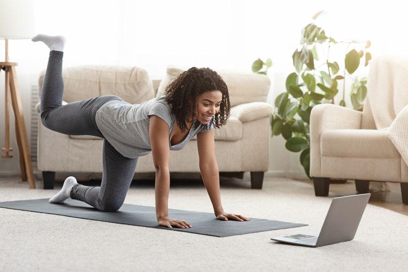 woman doing pilates bird dog pose with video
