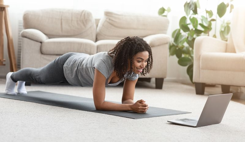 woman doing plank pose in living room with video