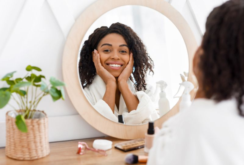smiling woman admiring her skin in the mirror