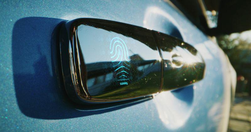 Close up shot of a woman using fingerprint reader to unlock car