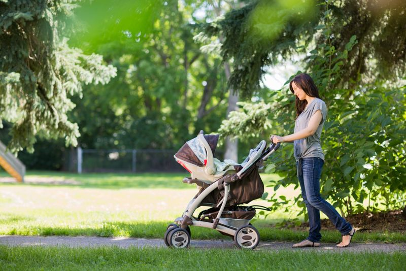 woman walking with her new baby in stroller