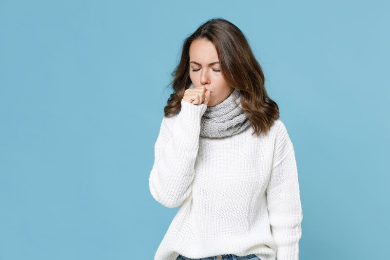 sick woman in warm clothing coughing