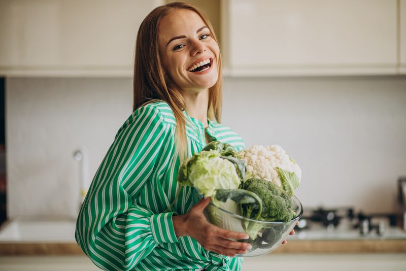smiling woman holding bowl of cauliflower and broccoli