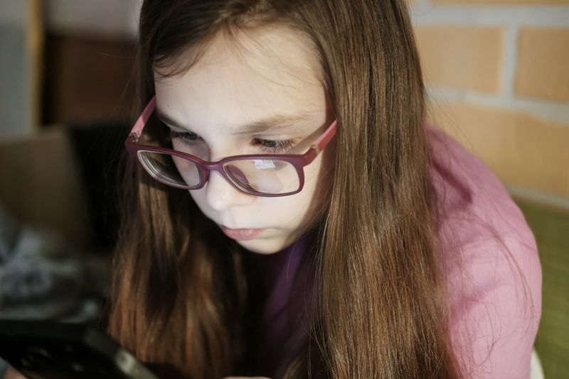 adolescent girl with glasses leaning into phone screen