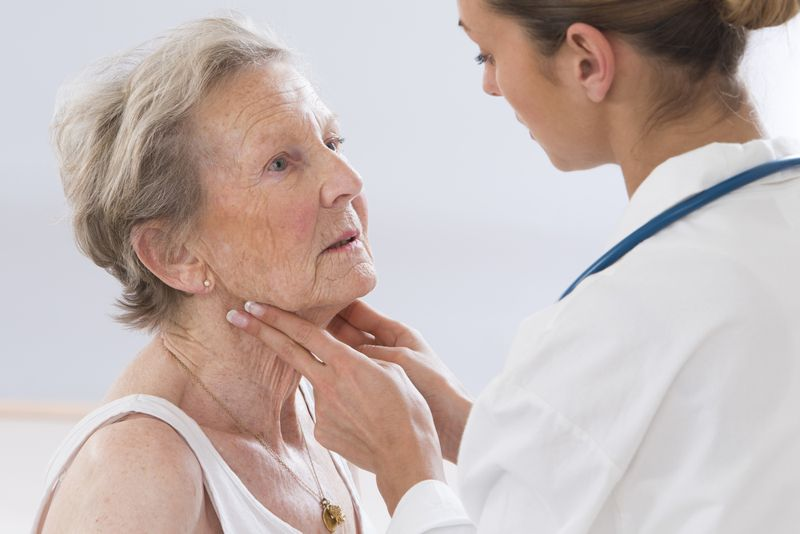 young female doctor feeling senior patient's throat