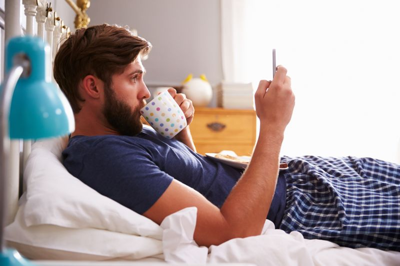 man in bed with coffee, checking his phone